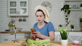 Girl with mask on face surfs internet on phone in kitchen. Girl in blue t-shirt with facial mask and head wrapped in towel surfs internet on phone at kitchen stock video
