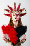Girl in mask with a fan in hands Stock Images