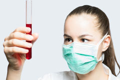 Girl in a mask holding test tube with red liquid - science concept Stock Photo