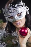 Girl in mask holds a red sphere Stock Image
