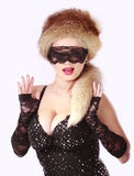 Girl in mask posing. Young busty girl in mask posing with fur hat, lace gloves Royalty Free Stock Photo