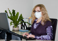 Girl in mask working at office royalty free stock images