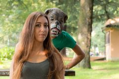 Girl and masked boy. Boy with a dog mask behind a beautiful girl in a green park Royalty Free Stock Images