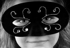 Girl in Masquerade Mask. Young girl wearing ornate masquerade mask
