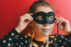 Girl in masquerade mask on a red background stock photo