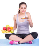 Girl on a mat choosing between fruits and sweets Royalty Free Stock Photography