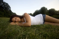 A girl in meadow. An early twenties caucasian females relax on a clear afternoon in a Connecticut, USA, meadow stock photography