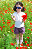 Pretty girl on the meadow. Pretty girl with bunch of red flowers on the meadow Stock Photo