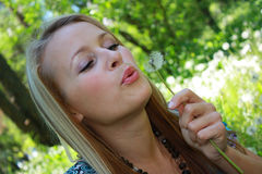 The girl on a meadow blows on dandelions Stock Photo