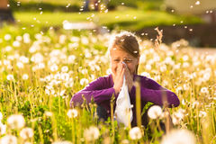 Girl in meadow and has hay fever or allergy. Girl sitting in a meadow with dandelions and has hay fever or allergy Royalty Free Stock Photos