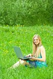 Girl  on meadow with laptop Stock Images