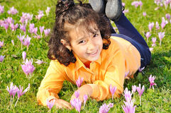 Girl on meadow with pink flowers arond Stock Photo