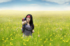 Girl on meadow pointing at camera Royalty Free Stock Photography