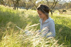 Girl on the meadow relaxing and using a laptop. Girl on the meadow with green grass relaxing and using a laptop Royalty Free Stock Photos