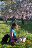Girl on the meadow relaxing and using a laptop. Girl on a meadow with green grass and blooming trees relaxing and using a white laptop Stock Photography