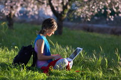 Girl on the meadow relaxing and using a laptop. Girl on a meadow with green grass and blooming trees relaxing and using a white laptop Stock Images