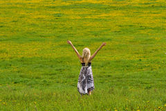 Girl on meadow in spring, arms. Young girl is standing on a meadow in spring, arms, raised royalty free stock photography