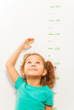 Girl measure height with hand looking up Stock Photo