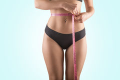 Girl measure her body. Pretty girl measure her body with a meter Stock Photos
