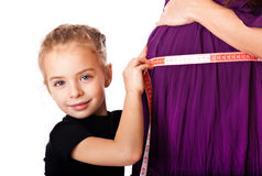 A girl measures the belly of her mother Stock Image