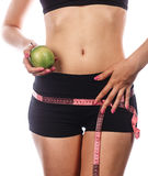 Girl measures buttocks and holding apple. Royalty Free Stock Photo