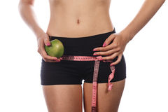 Girl measures buttocks and holding apple. Stock Image