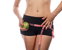 Girl measures buttocks and holding apple. Royalty Free Stock Photos