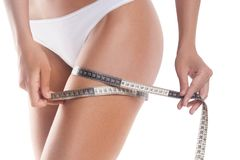Girl measures circumference of thigh. Fitness, weight loss and body care royalty free stock images