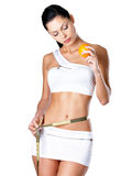 Girl measures figure with a measuring tape and holding orange Royalty Free Stock Photos