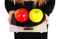 Girl measures the weight of apples Stock Image