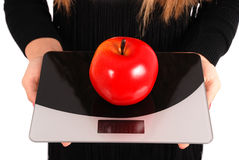 Girl measures the weight of apples Royalty Free Stock Photography
