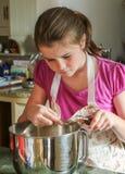 Girl measuring baking ingredients into a bowl Stock Photos