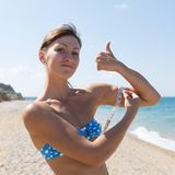 Girl measuring biceps looking at camera and showing thumb up. Athletic girl is measuring with a tape measure biceps and showing thumb up. Waist up portrait of royalty free stock photos
