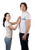 Girl measuring the chest of handsome muscular man Stock Images