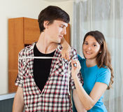 Girl measuring guy with measuring tape. Smiling girlfriend measuring guy with measuring tape Stock Photography