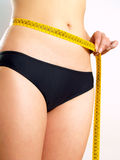 Girl measuring her abdomen after diet. Closeup photo of a Caucasian woman's abdomen. She is measuring her waist with a yellow metric tape measure after a diet Royalty Free Stock Photo