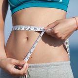 Girl measuring her waist. Sexy tummy and hands of young woman with measuring tape on open air Stock Image