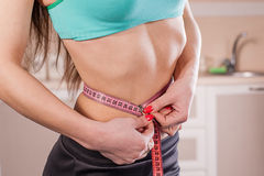 Girl measuring her waist Royalty Free Stock Image