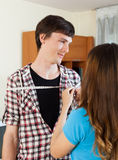 Girl measuring man with measuring tape Royalty Free Stock Photography