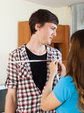 Girl measuring  shoulders  of boyfriend with measuring tape Royalty Free Stock Photography