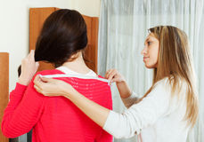 Girl measuring the shoulders of  friend shoulders. With measuring tape at home Stock Photos