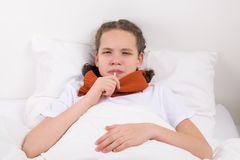 The girl is measuring the temperature with a thermometer in her mouth, lying in bed stock photos