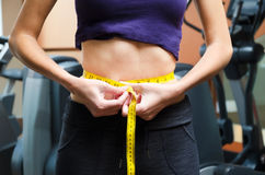 Girl is measuring waist. In the gym Royalty Free Stock Photo