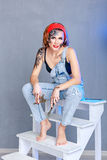 Girl mechanic with face art sitting on a stepladder. Stock Image