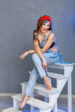 Girl mechanic with face art sitting on a stepladder. Royalty Free Stock Photo