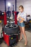 Girl mechanic replace tires on wheels. Sexy girl in shorts mechanic replace tires on wheels in the garage Stock Photo