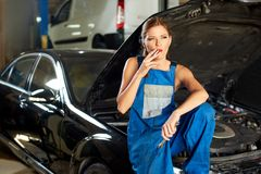 Girl mechanic smokes on the hood of a car in a car service. Girl mechanic smokes on the hood of a black car in a car service Royalty Free Stock Photos