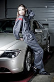 Girl in mechanic uniform. Young woman dressed in mechanic uniform leaning on silver car in garage Stock Photo