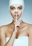 Girl in medical bandage after operation wants to keep her plastic surgery in secret. Royalty Free Stock Photo