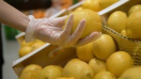 Girl in medical gloves chooses lemon in a supermarket. personal protection cocronovirus, vitamin C